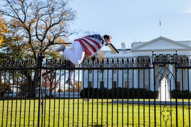 A man identified as Joseph Caputo is seen jumping the White House fence while wearing an American flag Thursday.